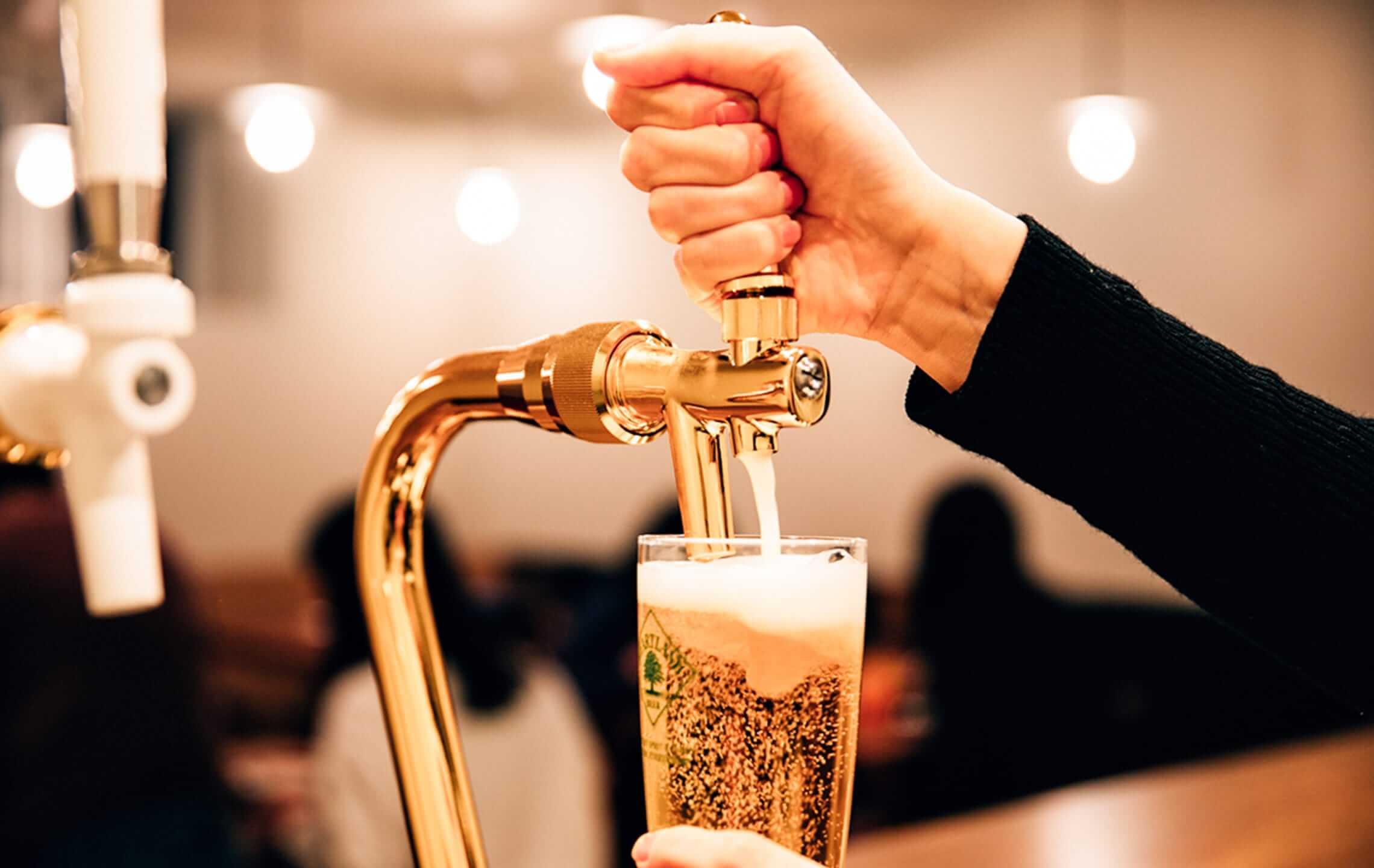 ビールを注ぎ入れている女性の画像